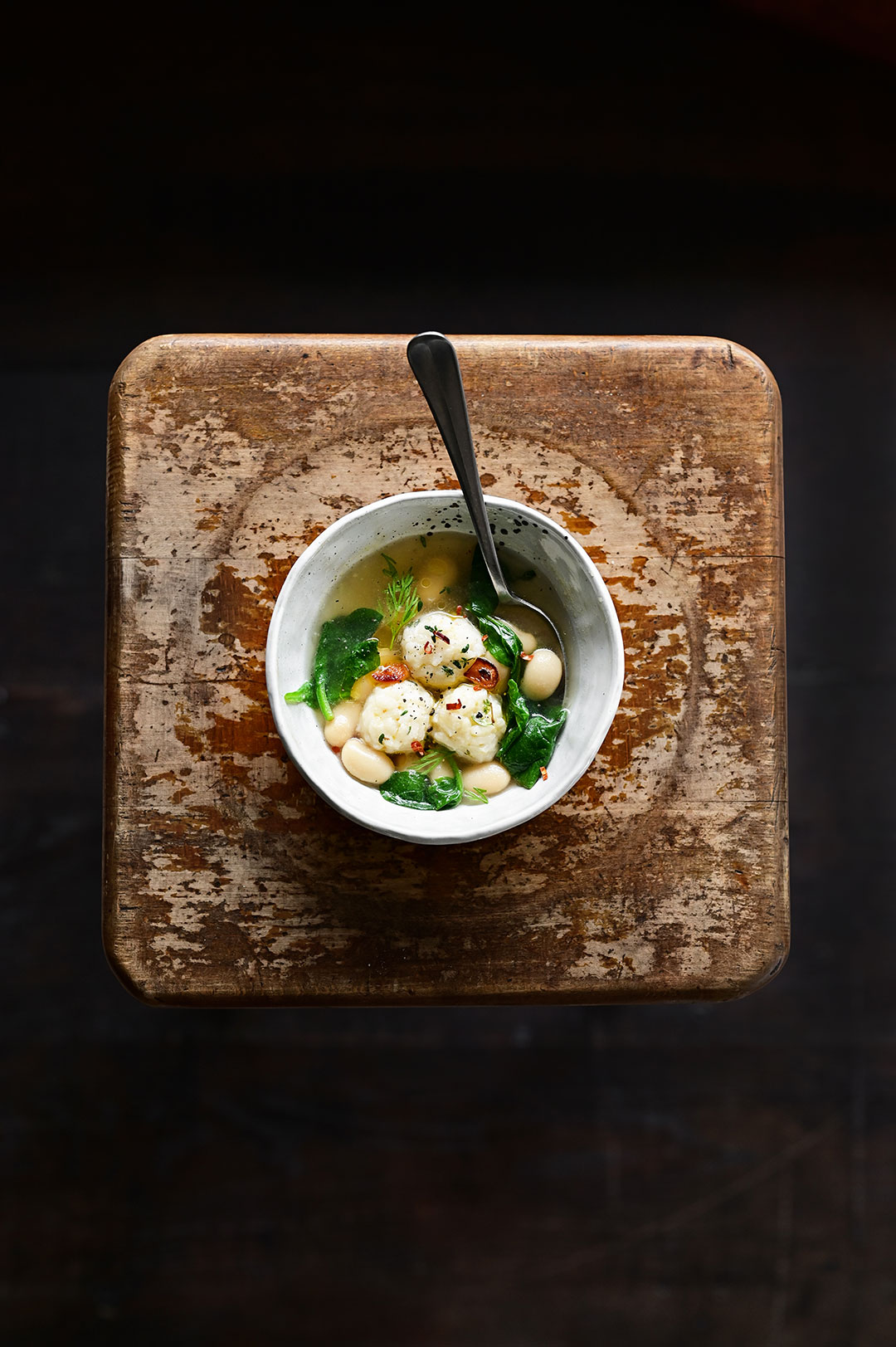 serving dumplings | Parmesan rice ball soup with spinach and butter beans