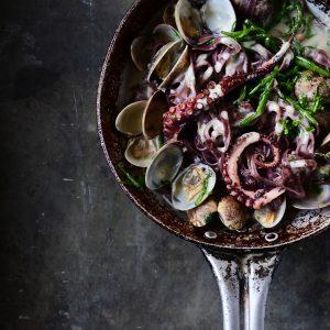 Zwarte pasta met kokkels en inktvis in een knoflooksausje